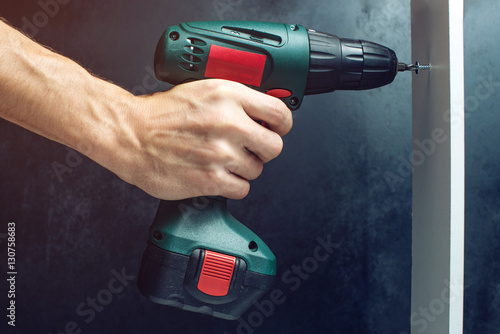Poster male hand holding a screwdriver, for screwing screws