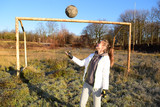 Beautiful sporty girl is in the old soccer field with a ball