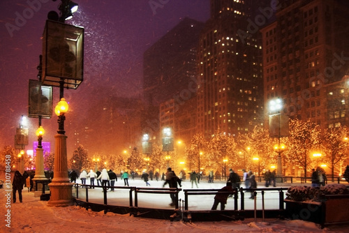 Fotobehang Chicago Winter night in Chicago. People enjoying ice skating at Millennium park ice rink during snowy night in Chicago.