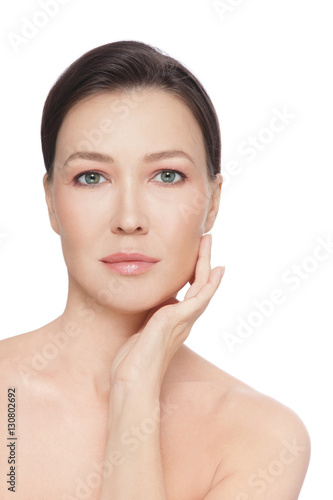 Beautiful healthy mature woman touching her face, over white background Poster
