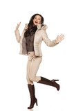 young happy woman in a winter jacket and boots jumping on a white background