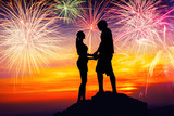 Happy couple together on rock and watching the fireworks