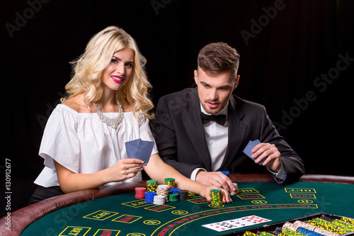 View of young, confident, man with the lady while he's playing poker game плакат