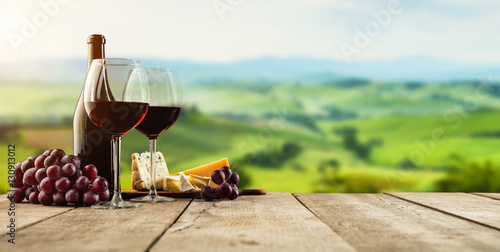Deurstickers Wijngaard Red wine served on wooden planks, vineyard on background