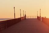 причал на закате а там ходит рыбак мужчина с удочкой