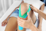 Fototapety Female knee with physio tape, closeup