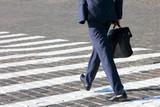Fototapety business man walks on a pedestrian crossing