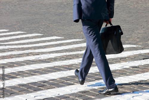 Plakat business man walks on a pedestrian crossing