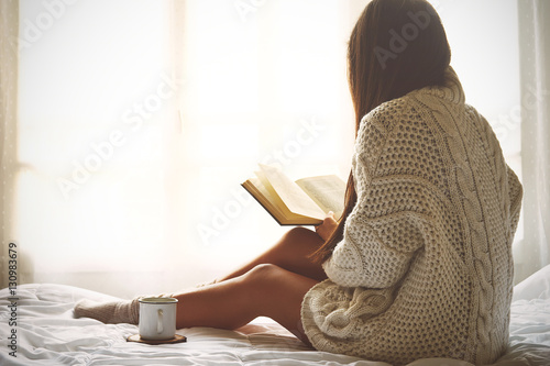 Young woman sitting in bed while reading a book - 130983679