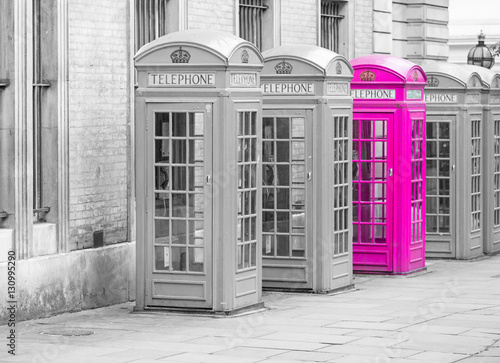 Five Red London Telephone boxes all in a row, in black and white with one booth in pink - 130995290