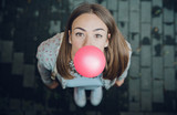 Top view of beautiful young brunette teenage girl blowing pink bubble gum - 131014053