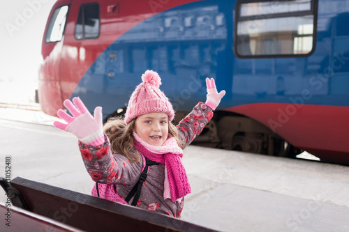 Poster Happy little girl at railway station