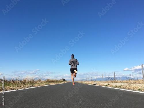 Zdjęcia na płótnie, fototapety, obrazy : Man running on open country path with winter blue sky