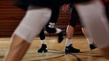 Low angle of basketball players running down a court