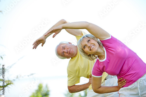 Active senior couple doing side bends in nature Poster