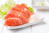 salmon sashimi on white dish and wood background