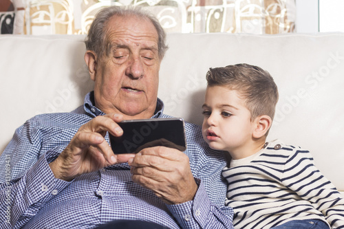 Grandfather and grandson looking a smart phone Poster