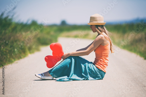Poster Lonely broken hearted woman is sitting on country road, intentionally toned