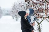 Motherkissing her daughter outdoor in winter