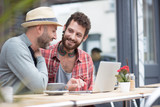 Gay couple sat sharing laptop outside cafe