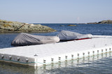 White plastic pontoon for boats and two covered boats