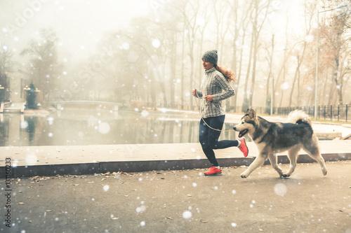 Fototapeta Image of young girl running with her dog, alaskan malamute