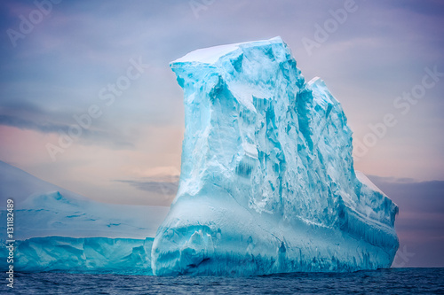 Tuinposter Antarctica Antarctic iceberg of unusual form in the snow floating in open ocean. Pastel sunset sky in the background. Beauty world.