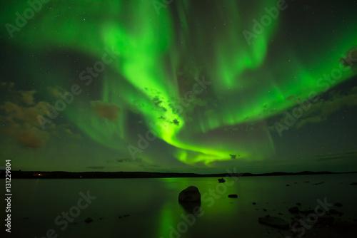Northern Night Sky - Bright aurora Borealis spreading cross the starry night sky over a lake.