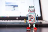 Blechroboter-Spielzeug, Methapher für Chatbot / Socialbot und Algorithmen, Laptop