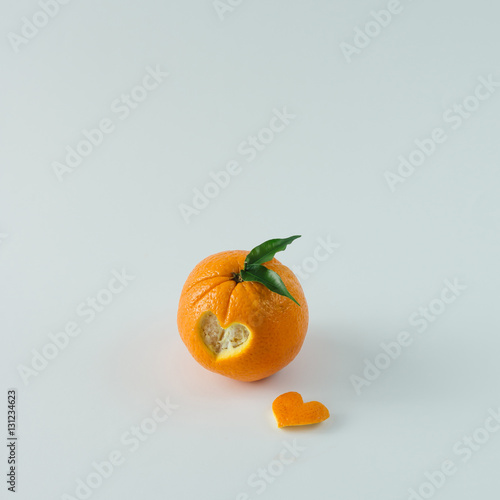 Orange with heart shaped cutout on white table. Minimal love con - 131234623