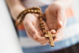Little boy child praying and holding wooden rosary.