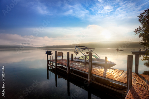 Poster, Tablou Sunrise through the clouds and mist over a calm New Hampshire lake