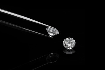 loose brilliant diamonds, one is being held by a tweezers on reflective black background