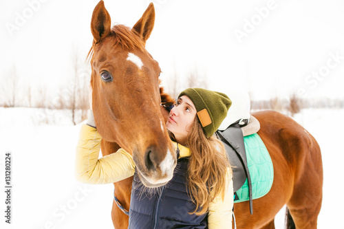 Female rider and horse in the open air. portrait of a beautiful young woman with her stallion, outdoors in winter. girl hugging and caressing the animal