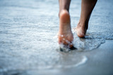 Fototapety Woman barefoot walking on the beach
