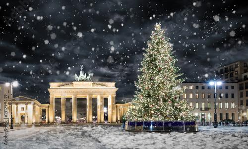 Brandenburger Tor in Berlin mit Weihnachtsbaum bei Nacht und Schneefall