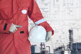 Engineer holding safery hetmet on refinery background