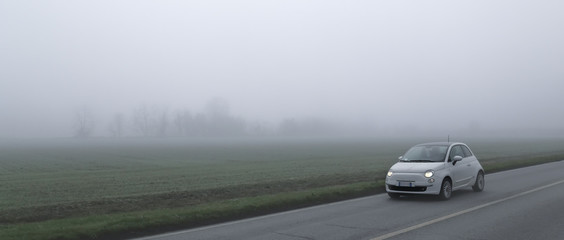 Small car runs along a country road on a foggy day