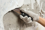 hand removing wallpaper from wall with spatula - 131319206