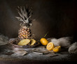 still life. pineapple, lemon, tropical juice, old silver knife on a wooden table