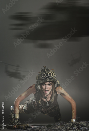 Poster The soldier on the battlefield with a gun fell to the ground and screams