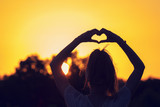 Girl making a heart-shape with her hands outdoors.
