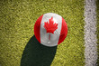football ball with the national flag of canada lies on the field