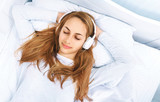 Girl in bed with a headphones on listening to the music