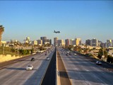 Urban landscape of city skyline and freeway with commercial plane landing
