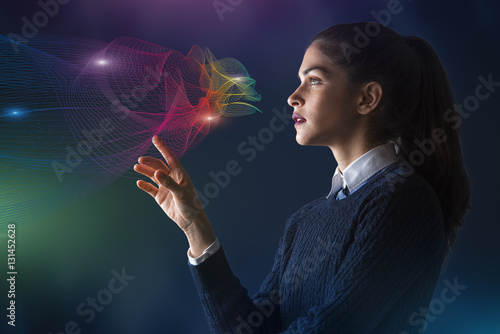 Poster concept of a young woman selecting colors on projected rainbow color spectrum ve