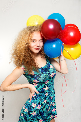 Poster teenage girl with helium balloons over gray background