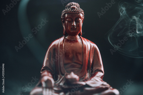 Foto op Canvas Boeddha Buddha statue with incense. Deity and symbols of Buddhism. The practice of Buddhism and its symbols. Spiritual life of Asia