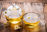 Glass of chamomile tea with full hot teapot with dried and fresh chamomile flowers on vintage old wooden table background