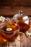 Glass of chamomile tea with full hot teapot and fresh chamomile flowers on vintage old wooden table background
